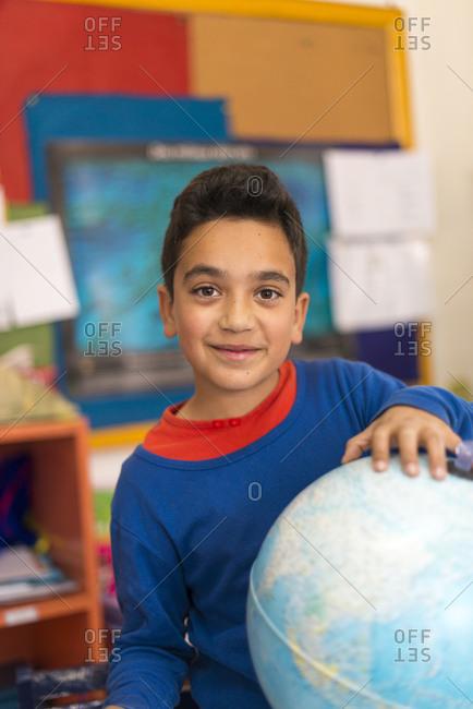 Kathmandu, Nepal - December 12, 2015: A boy sits next to a globe in a school in Kathmandu