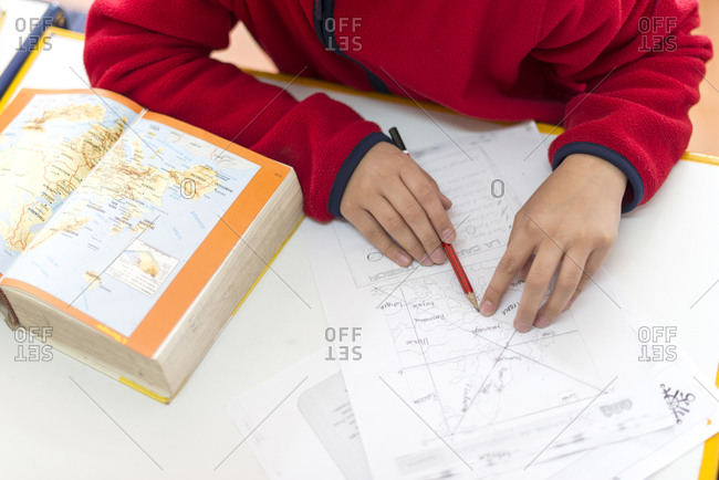 Kathmandu, Nepal - December 12, 2015: A child as a school in Kathmandu studies a map of the world
