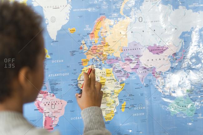 Kathmandu, Nepal - December 12, 2015: A child as a school in Kathmandu studies a map of the world on the wall