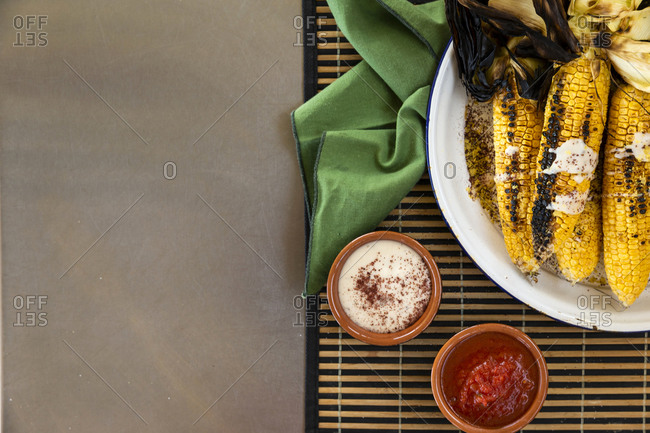 Grilled corn on plate beside sauces with copyspace