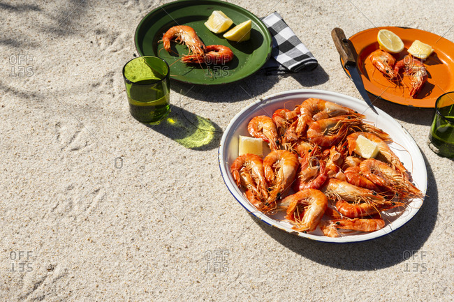 Cooked shrimp on plates in beachy setting with copyspace