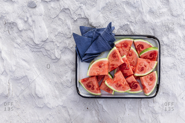 Slices of watermelon on tray on textured sandy background