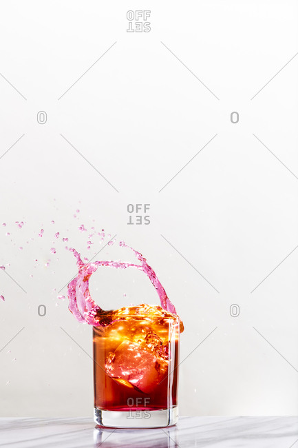 An ice cube dropped into a cocktail glass creates a dynamic splash of liquid against a white background