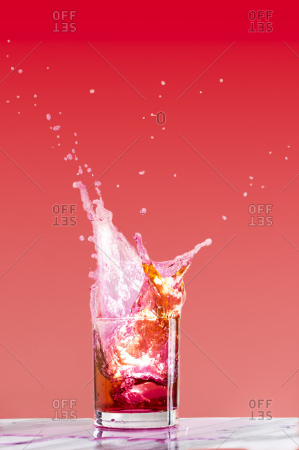 An ice cube dropped into a cocktail glass creates a dynamic splash of liquid against a pink background