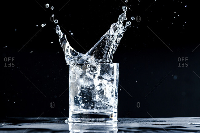 Sparkling water dynamically splashes out of a glass against a black background