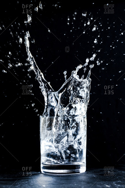 Sparkling water dynamically splashes out of a glass against a dark background