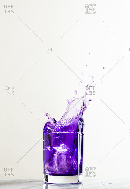 An ice cube dropped into a glass of purple beverage creates a dynamic splash against a white background