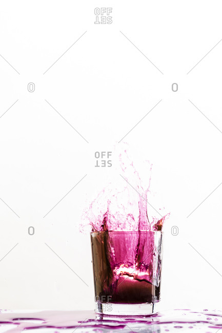An ice cube dropped into a pink drink creates a dynamic splash against a white background