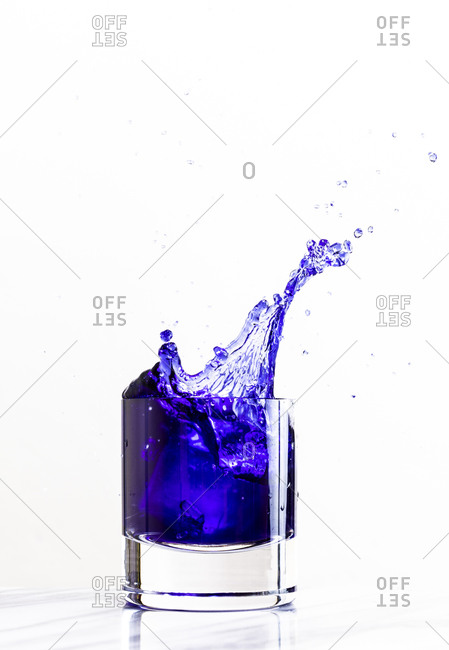 Ice dropped into a glass of purple beverage creates a dynamic splash against a white background