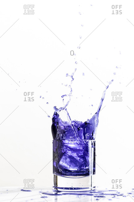 Ice dropped into a glass of purple beverage creates a dynamic splash on a white background