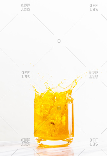 Ice cube dropped into a glass creates a bright yellow splash of liquid against a white background
