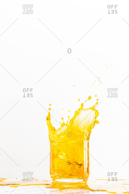 Ice cube dropped into a glass creates a bright yellow splash of liquid on a white background