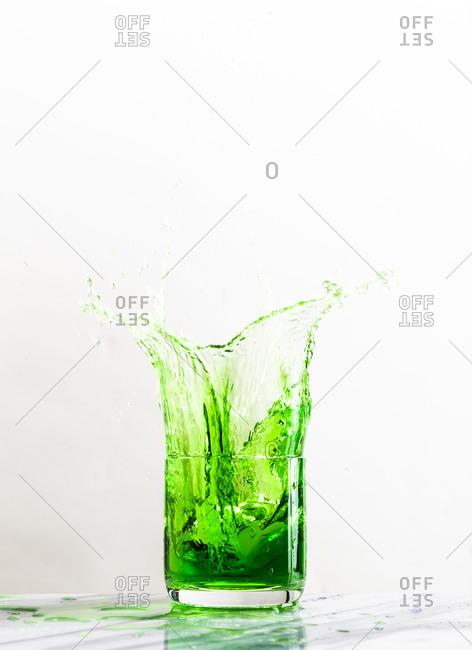 An ice cube creates a splash in a glass of green liquid