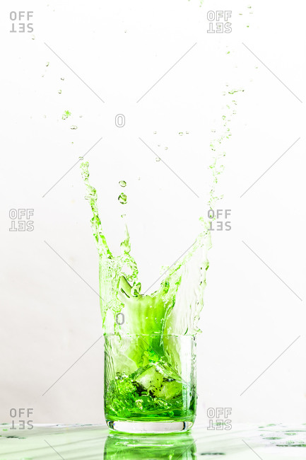 An ice cube creates a splash in a glass of green liquid on white background