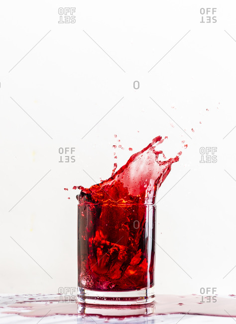 Red beverage splashes out of a glass after an ice cube is dropped into the liquid