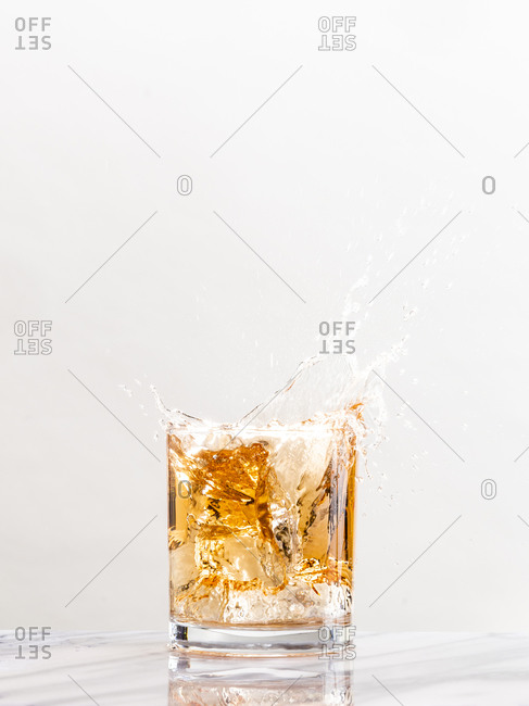 An ice cube creates a splash in a glass of golden alcohol in a cocktail glass against a white background