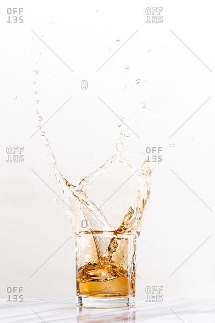 Ice creates a splash in a glass of golden alcohol in a cocktail glass against a white background