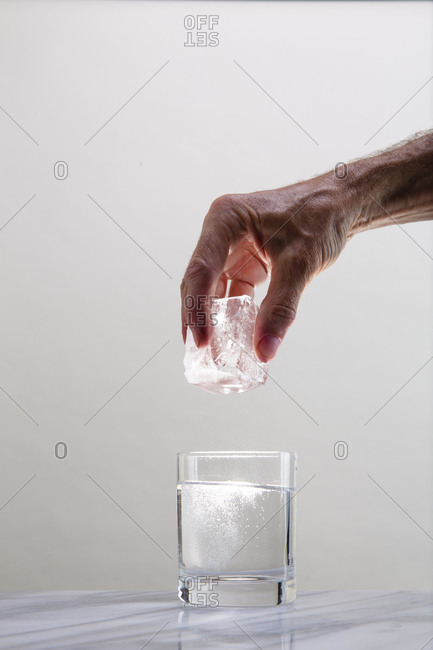 A large cube of cocktail ice is held above a glass of clear liquid