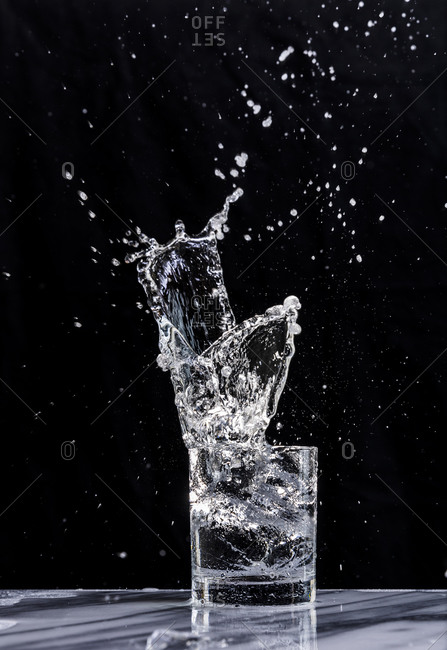 An ice cube creates a splash in a glass of sparkling water in a cocktail glass against a black background