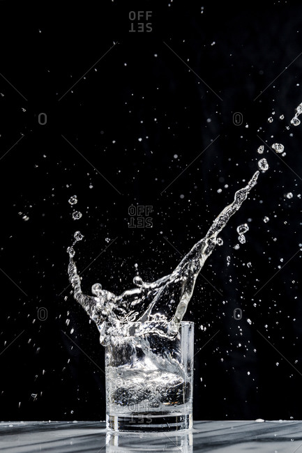 Ice creates a splash in a glass of sparkling water in a cocktail glass against a black background