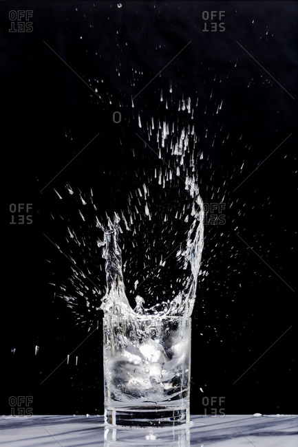 Action shot of ice creating a splash in a glass of sparkling water in a cocktail glass against a black background