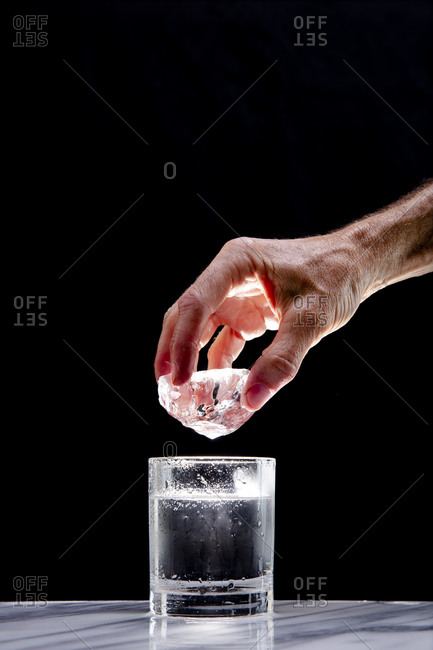An ice cube is about to be dropped into a dramatically lit glass of water