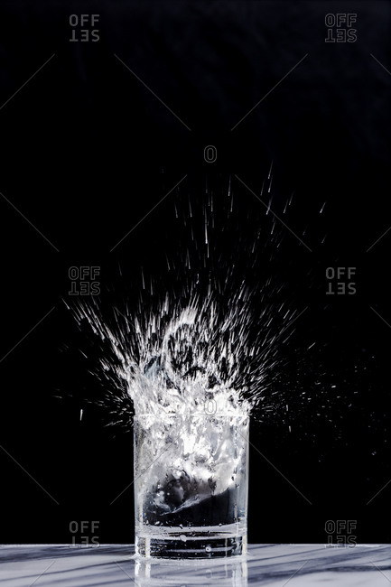 Ice splashing into a glass of sparkling water in a cocktail glass against a black background