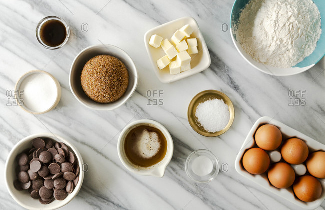 Overhead spread of ingredients for chocolate chip cookies on a marble countertop