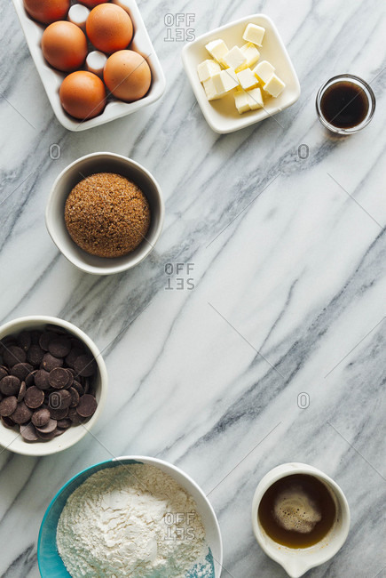 Overhead spread of ingredients for chocolate chip cookies on a marble countertop with open space for text