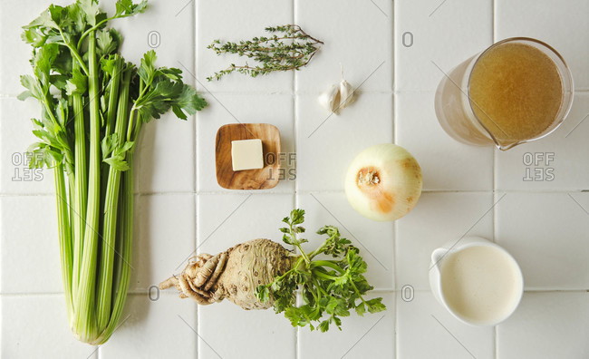 Overhead spread of ingredients for celery soup against while tile counter
