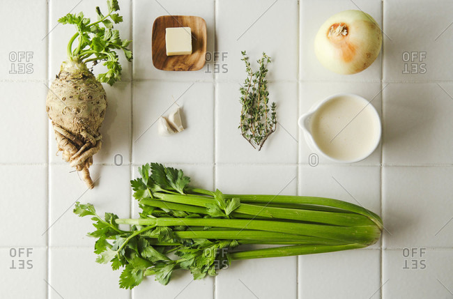Overhead spread of ingredients for celery soup against while tile