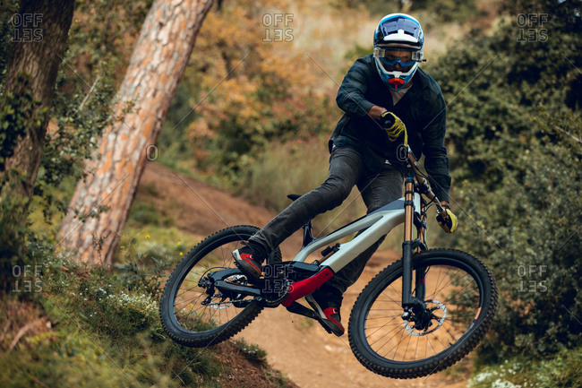 Unrecognizable man in helmet, gloves and protection glasses jumping doing whip trick downhill during mountain biking practice in wood forest
