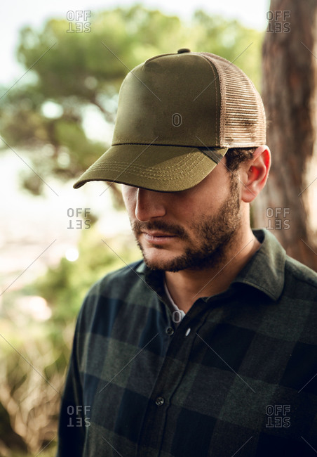 Unrecognizable portrait of brunet man in checkered shirt and baseball cap standing in nature background looking down