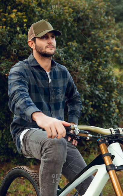 Mountain biking sportsman without protection sitting on bike in the middle of a forest looking away