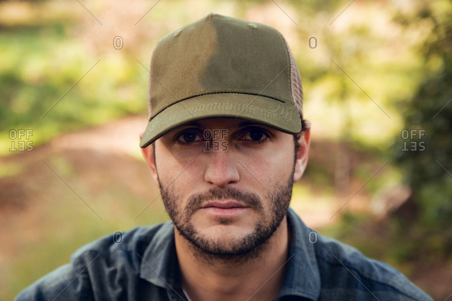 Portrait of handsome brunet man in checkered shirt and baseball cap standing in nature background looking at camera