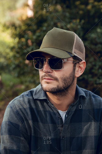 Portrait of handsome brunet man in checkered shirt and baseball cap standing in nature background looking away
