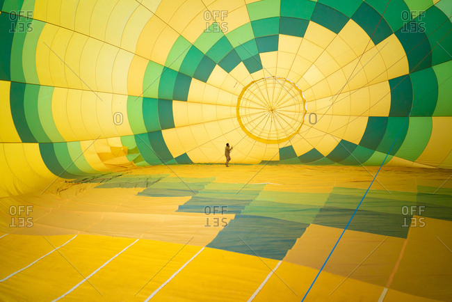 Unrecognizable man checking condition of large green and yellow air balloon while standing inside and conducting maintenance