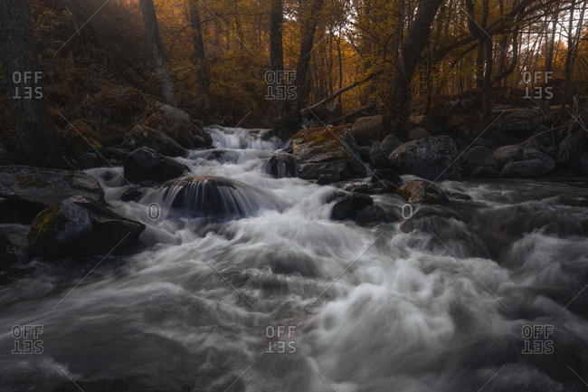 Breathtaking scenery of small waterfall in autumn dense forest