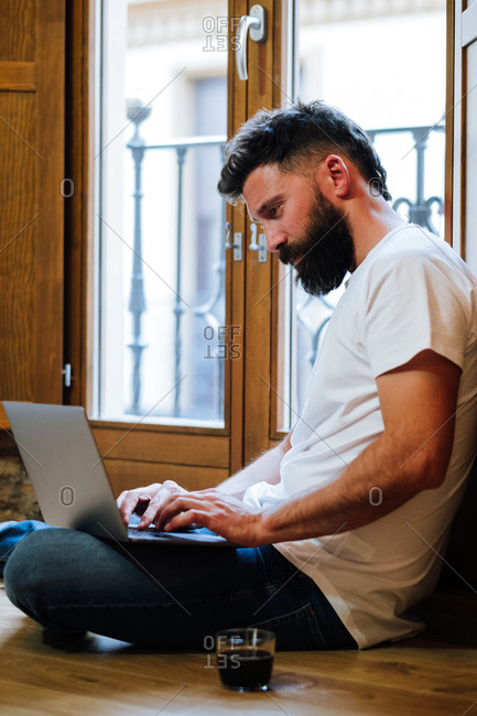 Side view of bearded man sitting on floor near mug of hot beverage and typing on laptop while working on remote project at home