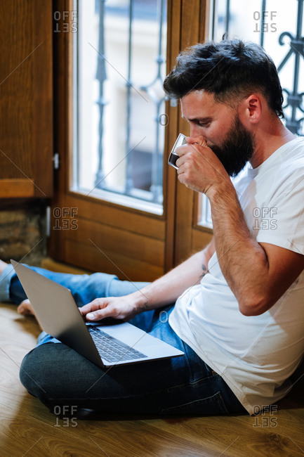 Bearded man sipping hot drink and reading data from laptop while sitting on floor and working on remote project at home