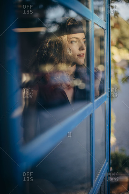 Young smiling female in black bodysuit looking away pensively and smiling while standing near window at home