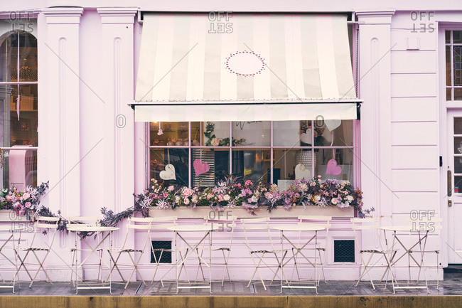 Facade of empty terrace of modern cafe with pink wall and window decorated with flowers and hearts on city street