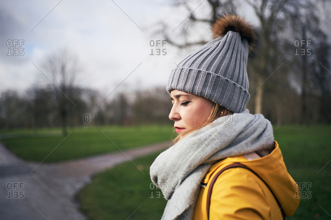 Side view of calm young female in trendy outerwear with scarf and hat standing in park with green grass and leafless trees
