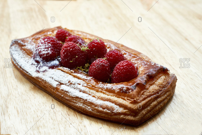 From above of yummy homemade puff pastry with fresh strawberries and sugar powder placed on wooden table