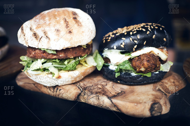 Delicious white and black burgers with green lettuce and cheese served on wooden board on black table