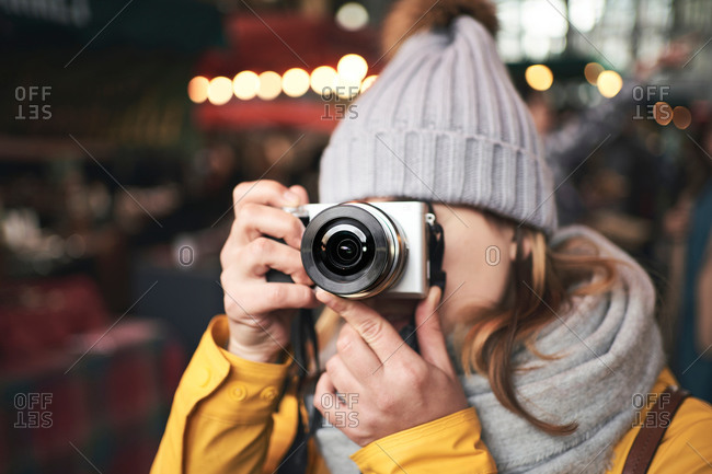 Unrecognizable female traveler in warm clothes taking pictures with camera while standing on city street with illumination in winter evening