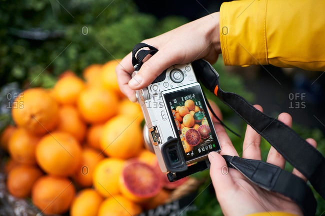 From above of crop anonymous person with digital photo camera taking picture of ripe orange fruits while visiting grocery market