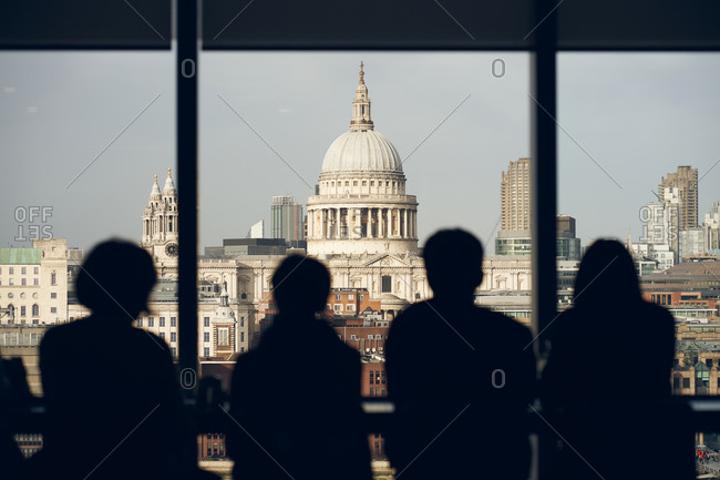 Back view silhouettes of travelers standing near window at viewpoint and admiring view of Saint Paul Cathedral in London