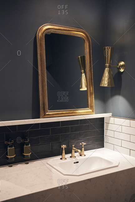 Mirror with golden frame hanging on black wall near lamp over marble counter with sink in elegant bathroom