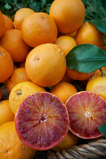 From above halves of red orange placed on heap of citruses in basket on marketplace